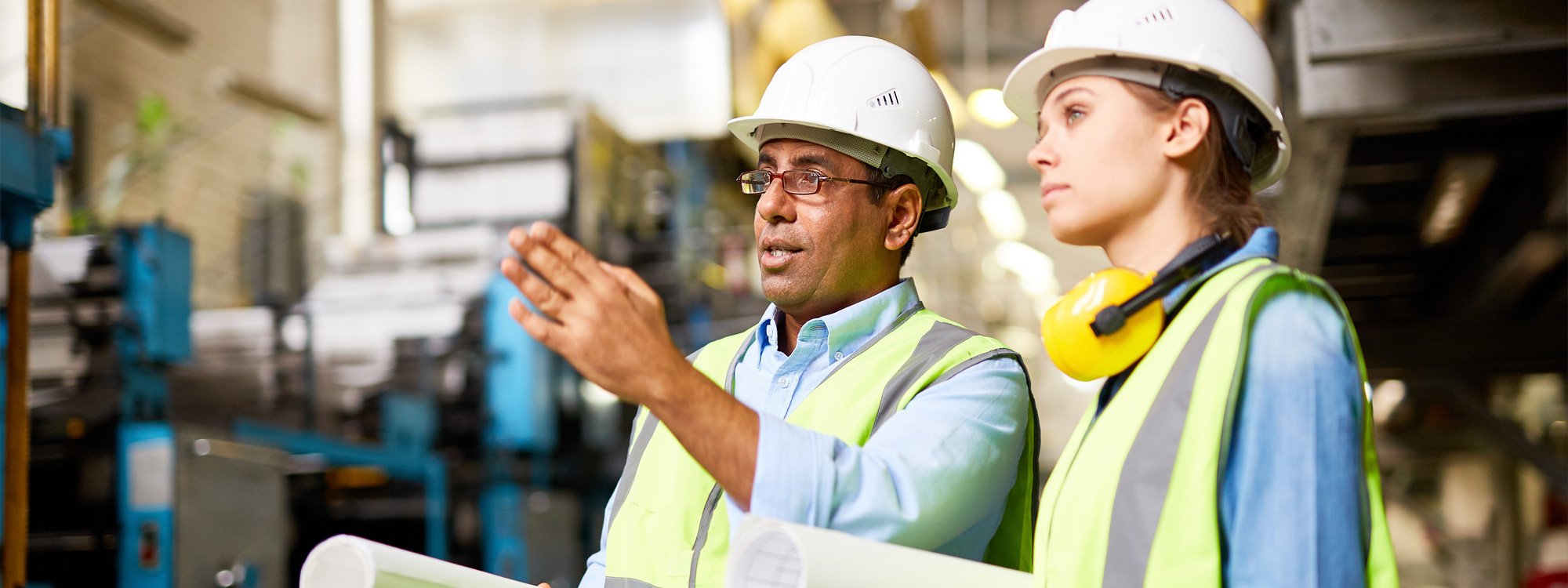man in hard hat talking to woman in hard hat and point elsewhere